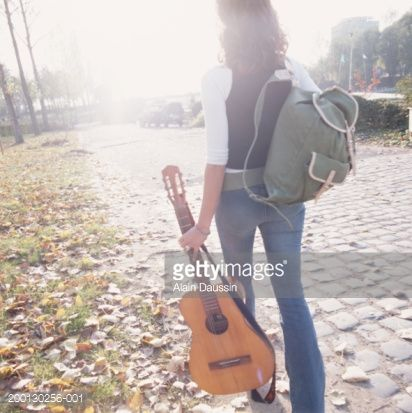 young-woman-carrying-acoustic-guitar-outdoors-rear-view-picture-id200130256-001?s=170667a.jpg